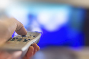 Close up of remote in hand with shallow depth of field during television watching