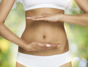 Pregnancy or diet concept, female hands protecting the stomach over nature background